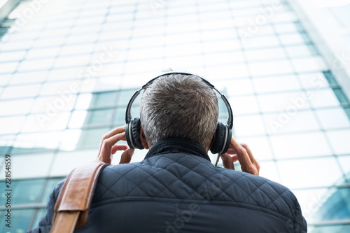 streaming écouter musique casque audio chanson radio plaisir agréable blockchain casual quarantaine street voyager podcast dos homme building immeuble - 228541559