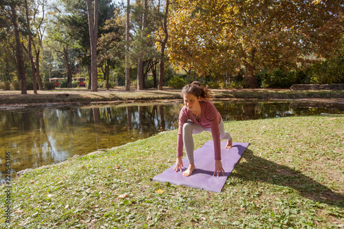 Woman Practising Yoga On Exercise Mat In Park