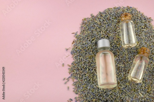 Essential lavender oil .lavender oil set in glass bottles in the seeds of lavender on a light pink background.Organic Pure Natural Oils