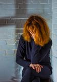 eine Frau sitzt traurig vor einer Wand - 228545549