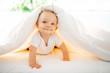 Leinwanddruck Bild - Cute baby girl lying on white sheet at home
