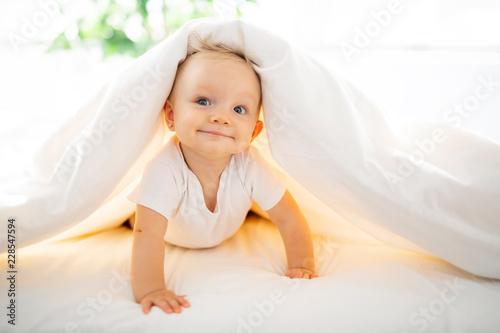 Leinwanddruck Bild Cute baby girl lying on white sheet at home