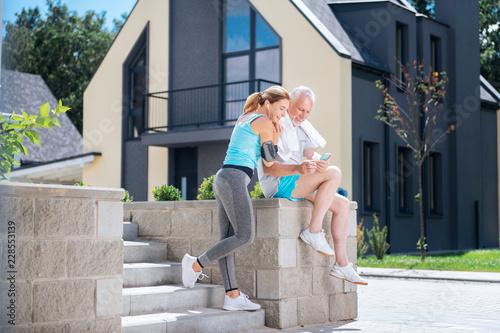 Dopasuj kobietę. Dopasuj kobieta nosi szare legginsy i białe trampki stojący w pobliżu jej lekkoatletycznego mężczyzna po niesamowity poranek sportu