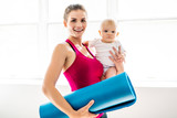 A Portrait of beautiful young mother in sports wear with her charming little baby in training session - 228555546