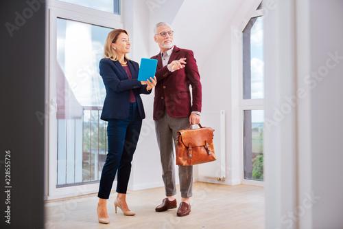 Piękny agent. Stylowy agent nieruchomości na sobie niebieski strój rozmawia z jej klienta, stojąc w fantazyjne mieszkanie