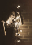 Portrait of a young woman with fairy lights outdoor
