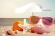 Leinwandbild Motiv Summer piggy bank with sunglasses on the