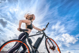 Athletic girl with hair flying in the wind leading electric bike. - 228586975