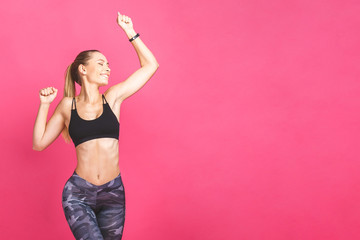 Weight loss fitness woman jumping of joy. Young sporty caucasian female model isolated on pink background. © denis_vermenko