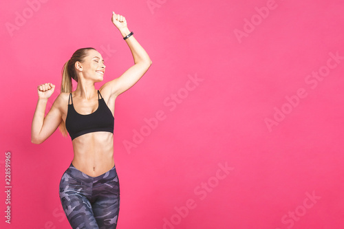 Fototapeten Fitness Weight loss fitness woman jumping of joy. Young sporty caucasian female model isolated on pink background.