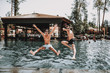 Young Smiling Friends Jumping into Swimming Pool