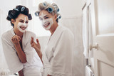 Two smiling women in bathrobes applying face cream