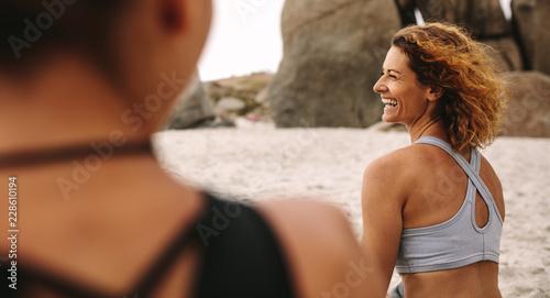 Sticker Cheerful women in fitness wear sitting on the beach