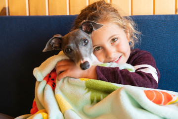 Child with dog on her hand on sofa © pololia