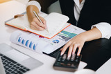 Business woman holding a pen to analyze the marketing plan with calculator on wood desk in office. Accounting concept.Finance concept. - 228621526