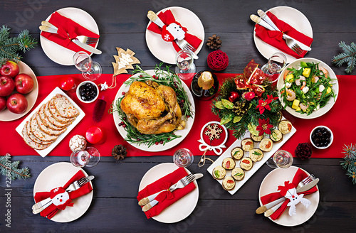 Baked turkey. Christmas dinner. The Christmas table is served with a turkey, decorated with bright tinsel and candles. Fried chicken, table.  Family dinner. Top view - 228628719
