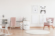 Stylish scandinavian nursery with white furniture and pink accents, cute poster on the white empty wall with copy space