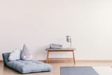 Futon with cute pillows on the floor of stylish baby room interior with copy space on the empty white wall