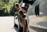 Children walking through the road between cars. Dangerous passage - 228644744