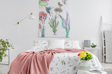 Powder pink blanket thrown on king-size bed with floral bedding in real photo of white bedroom interior with painting on the wall - 228644767