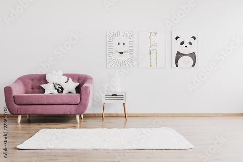 Stylowa różowa kanapa z uroczymi poduszkami w przestronnym pokoju dziecięcym wnętrza ze zwierzętami plakaty na ścianie