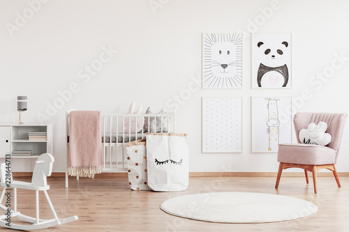 Stylish scandinavian nursery with white furniture and pink accents, cute poster on the white empty wall with copy space © Photographee.eu