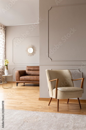 Leinwandbild Motiv Bright carpet in front of armchair in grey living room interior with wall with molding. Real photo