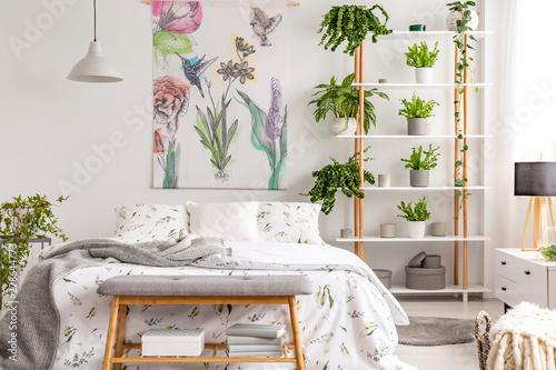 Prawdziwe zdjęcie wnętrza sypialni białe z wielu świeżych roślin, łóżko king size, materiał malarstwo z kwiatowy wzór i ława z książek