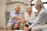 Senior couple shaking hands with financial advisor