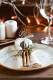 Decorated Thanksgiving or New Year table setting among white candles and winter decor. The concept of a festive dinner. - 228645353