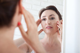 Woman looking at wrinkles in mirror. Plastic surgery and collagen injections. Makeup. Macro face. Selective focus - 228652774