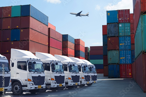 Container depot service with truck, reach stacker and shipping containers on yard at background.