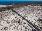 Vista aerea di una strada che attraversa campi di lava tra le coste frastagliate di Lanzarote, Isole Canarie, Spagna, Africa. Natura selvaggia. Sabbia e dune