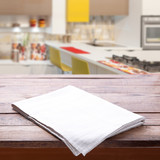 Kitchen towel on empty wooden table. Napkin close up top view mock up for design. Kitchen rustic background. - 228669349