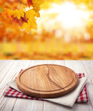 Autumn landscape and pizza board with napkin on wooden table. Top view mock up - 228673372