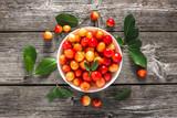 Yellow cherry on plate on wooden table, sweet cherries, fresh fruit, overhead