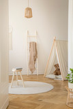 Vertical view of white scandinavian playroom with tent, teddy bear and wooden ladder with beige blanket, real photo - 228680322