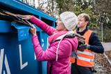 Frau und Mann entsorgen Altpapier in Container - 228687700