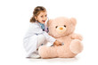 kid dressed in doctors white coat with stethoscope playing with teddy bear isolated on white