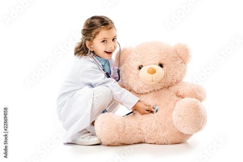 dziecko ubrane w lekki biały płaszcz z stetoskop gry z misiem na białym tle