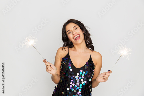 Leinwandbild Motiv celebration, fun and holidays concept - happy young woman in sequin dress with sparklers at party