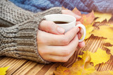 Woman's hands holding hot cup of coffee on the table with autumn leaves and knitted scarf.