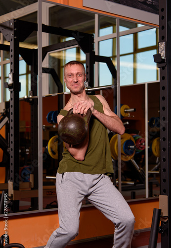 Poster Muscular man exercising in the gym. Sporty adult man with a kettle bell. Fitness, sport concept.