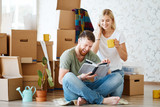 young couple with book sitting on floor while moving into new home - 228718195