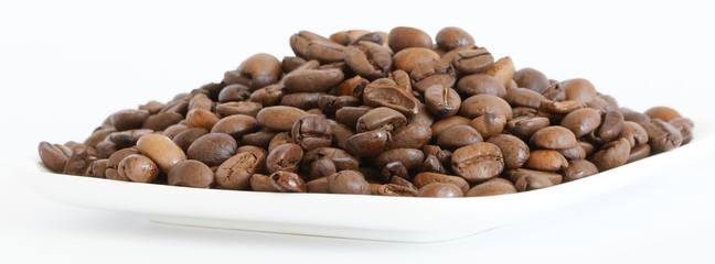 Many brown roasted coffee beans close-up isolated on white © Владимир Журавлёв