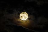 Full moon rising behind dark clouds