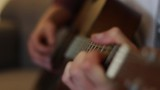 A young man is playing guitar, the focus racks from chord hand to strumming hand and back again. - 228775599