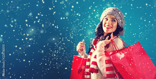 Leinwanddruck Bild Happy young woman holding shopping bags in a snowy night