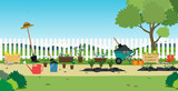 Garden plants and agricultural equipment with white fence. - 228788782
