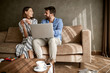 couple spending time at home, sitting on bed with laptop..